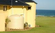 cream white water tank near beach 13500 litres